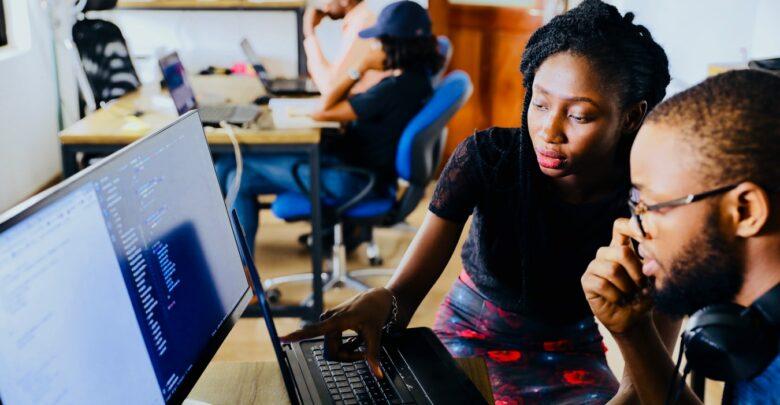 Des jeunes filles et jeunes hommes qui apprennent l'informatique.