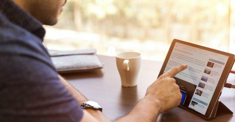 Une personne manipulant sa tablette au travail.