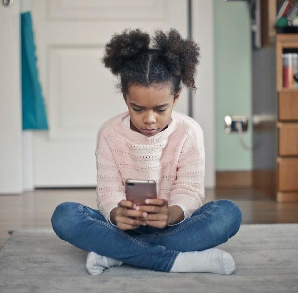 Une petite fille jouant avec son smartphone.